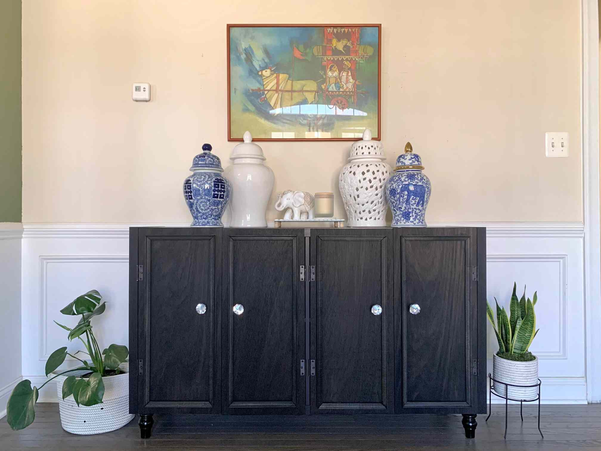 Black credenza with blue and white ceramic vases on top