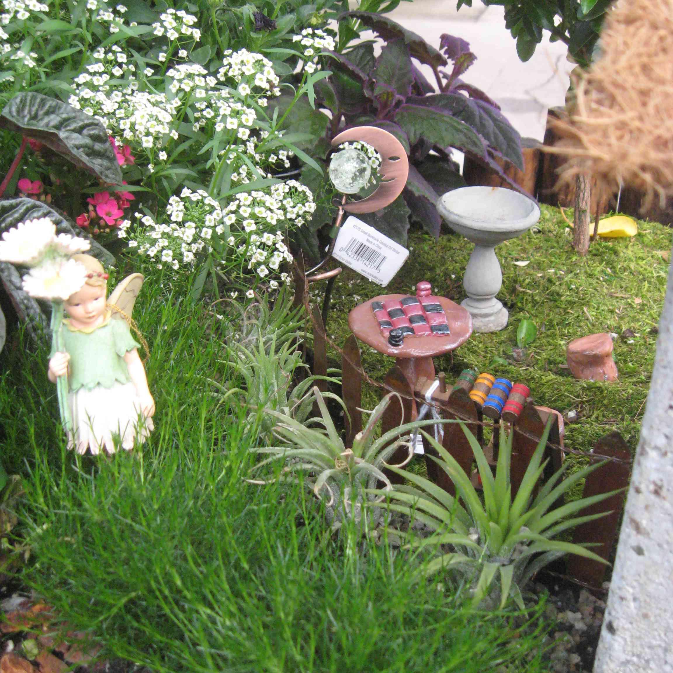 Miniature furniture and fairy statue in garden.