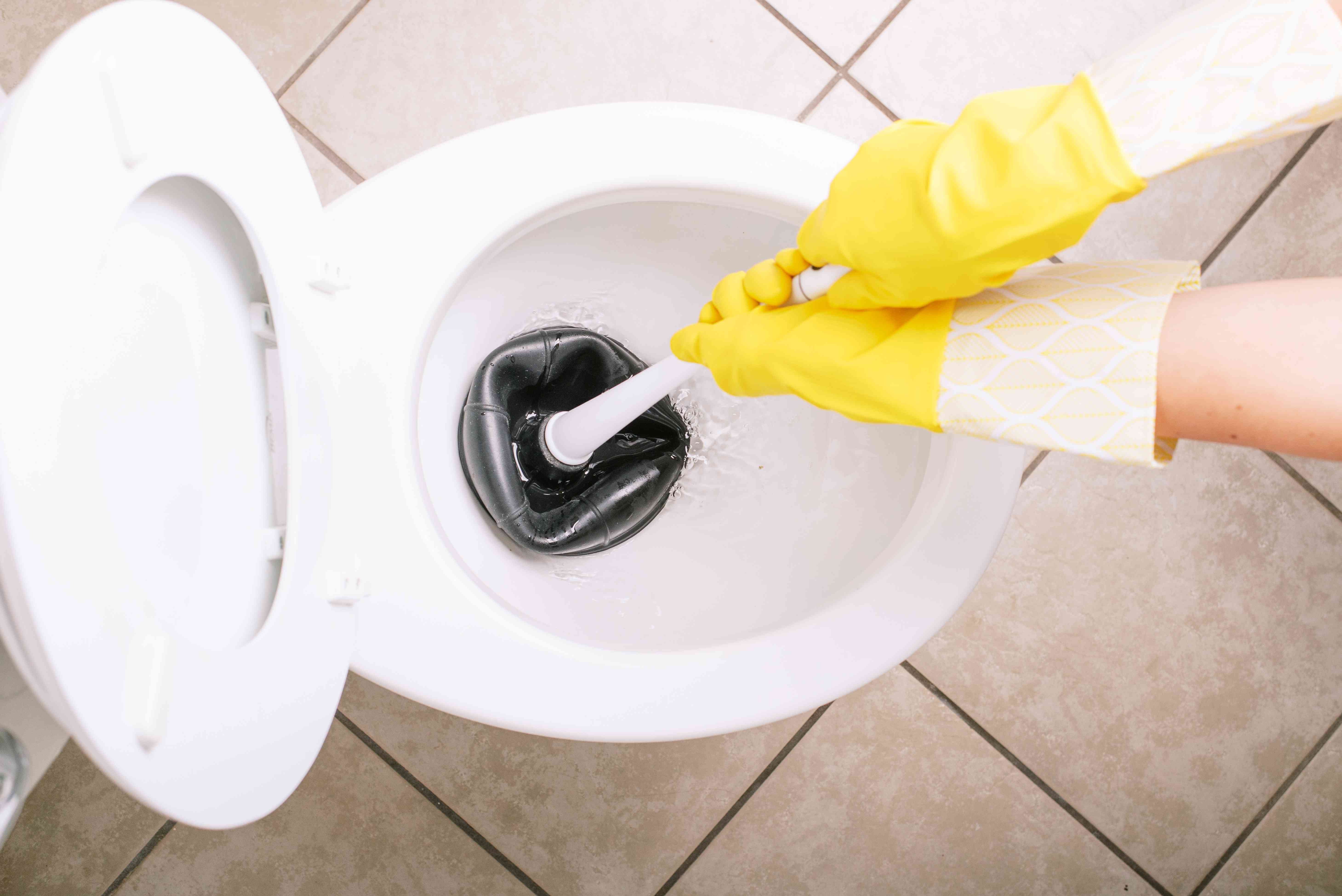 White ceramic toilet plunging out water with black plunger and yellow gloves