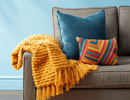 A couch with throw pillows and a yellow throw blanket