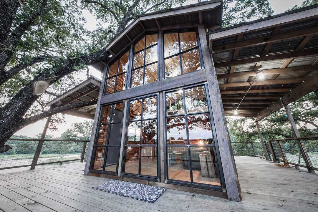 Tree house with lots of windows and a balcony