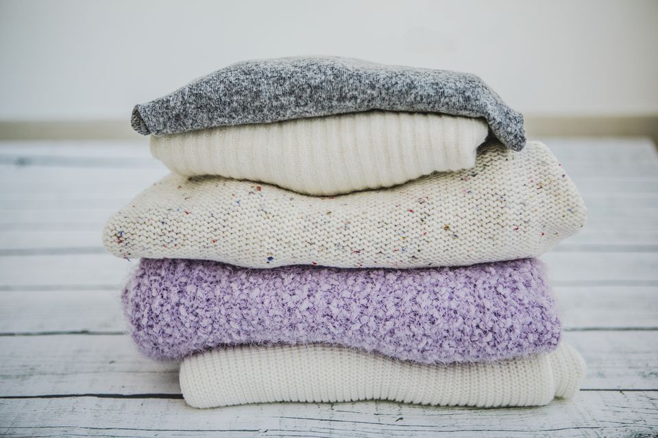 Variety of sweaters piled up.