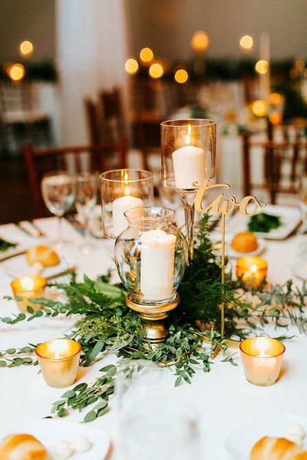 Centro de mesa moderno para bodas de invierno en verde y velas