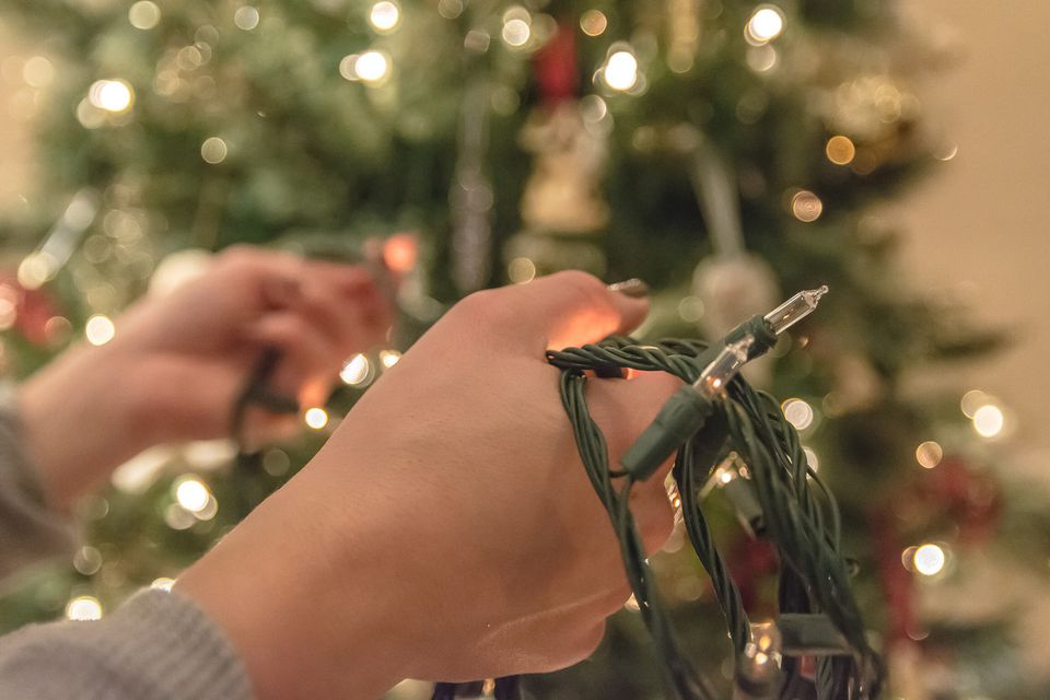 Hands fixing christmas lights that went out