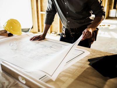 Building contractor reviewing blueprints