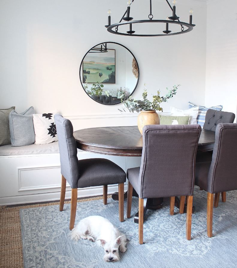 Updated dining room with bench seat and dog laying on rug.