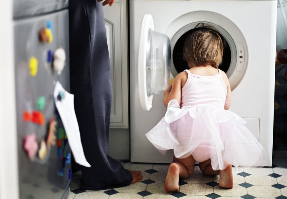 A girl in a dress looking into a washing machine