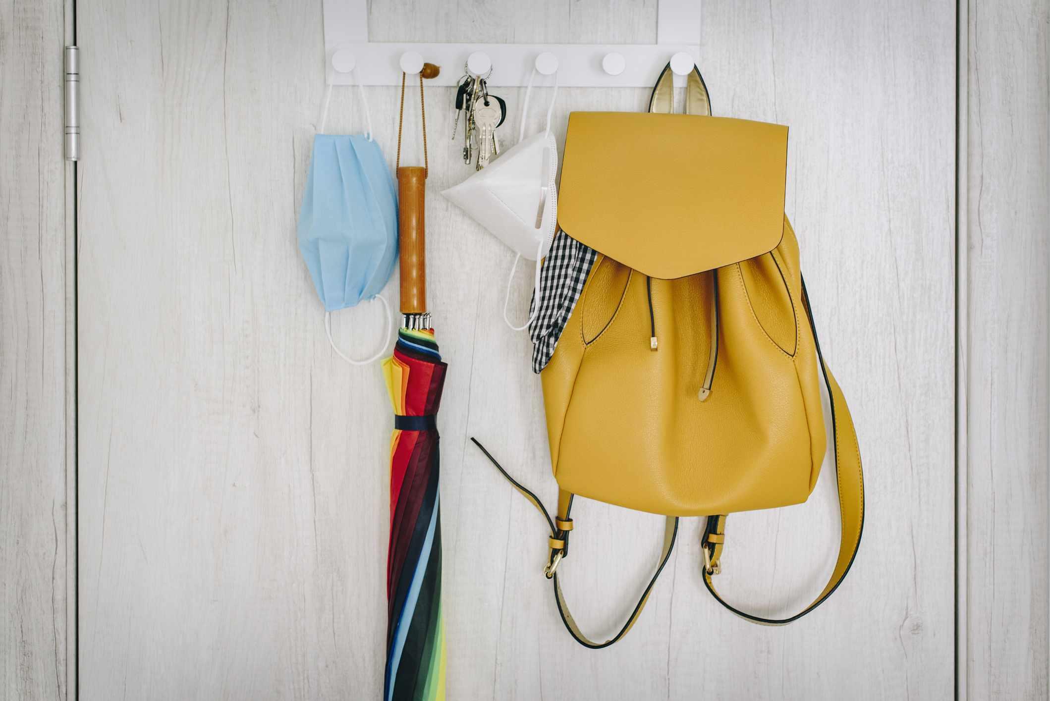 backpack, umbrella, and face masks on coat hooks