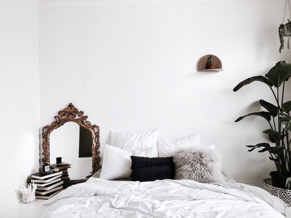 A white bedroom with neutral accents and a green plant