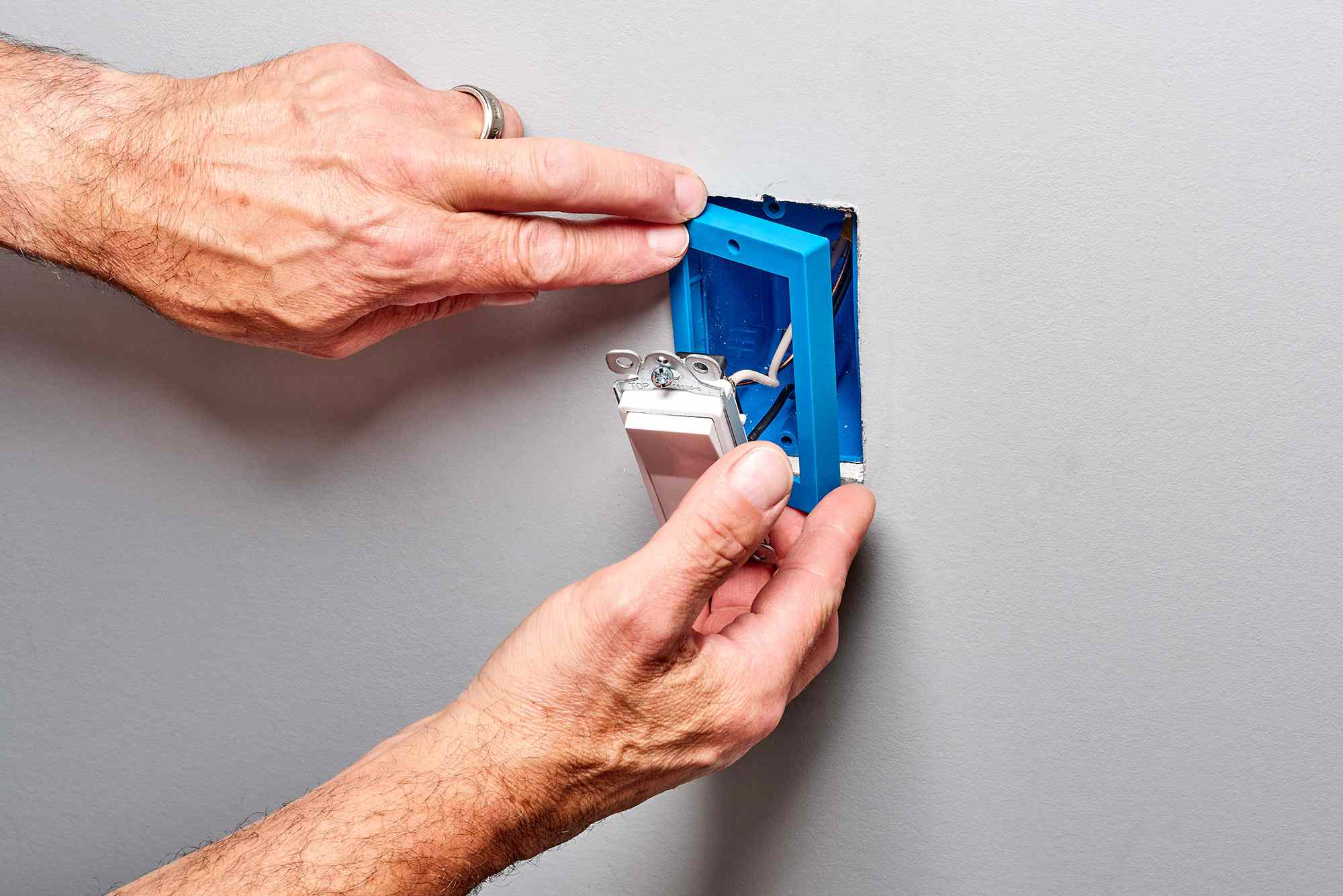 Blue box extender being slipped over the electrical box while holding the switch