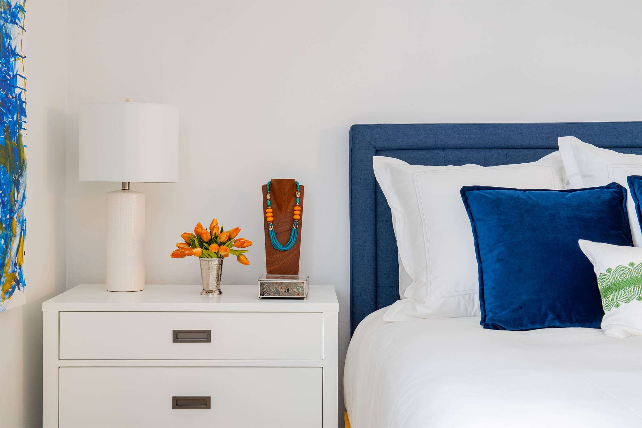 blue and white bedroom, small bouquet or orange flowers on nightstand