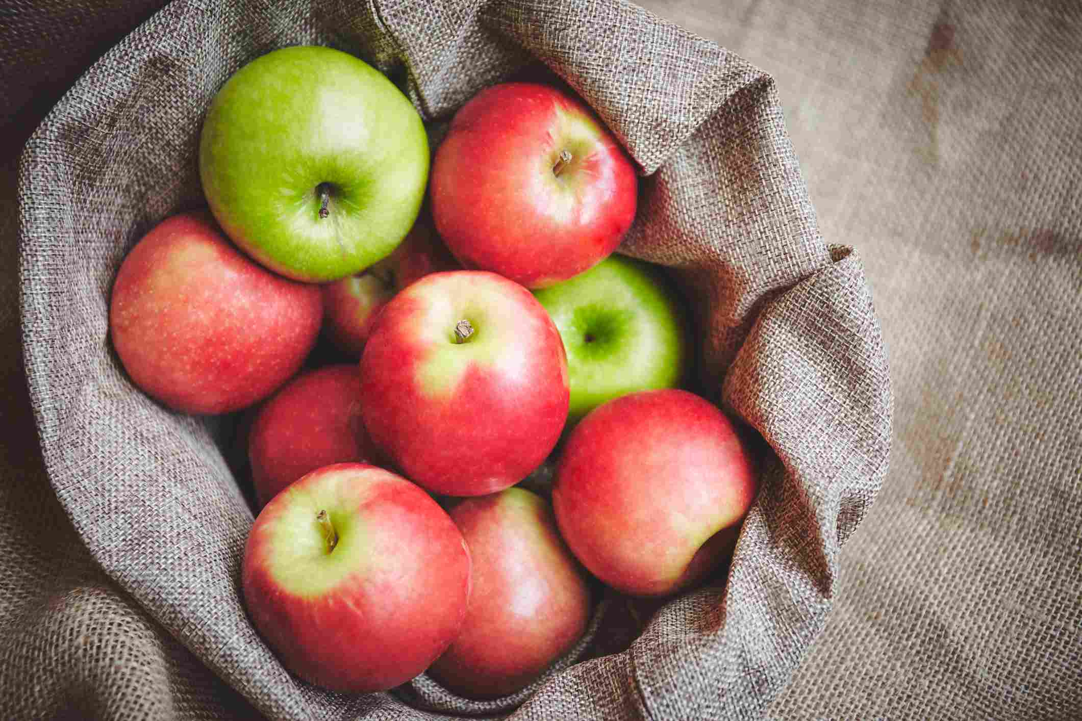 Green and red apples in a sack