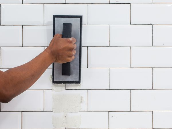 Ceramic white tile covered in white grout with rubber grout float