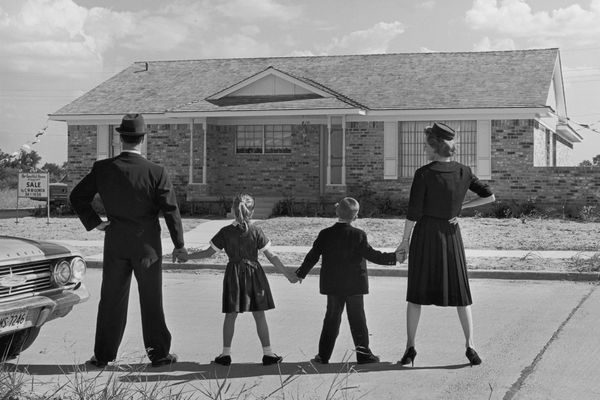 Image of a family of four holding hands while standing in a line with their backs to the camera, facing a ranch-style house in a suburban development. A sale sign is posted in the front yard of the house.
