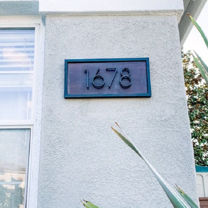 A modern house number sign made with wood.