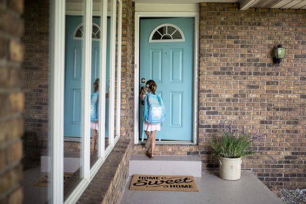 Girl with backpack opening door of house