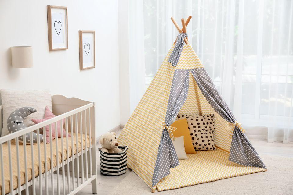 Interior acogedor de la habitación del bebé con carpa de juegos y cuna