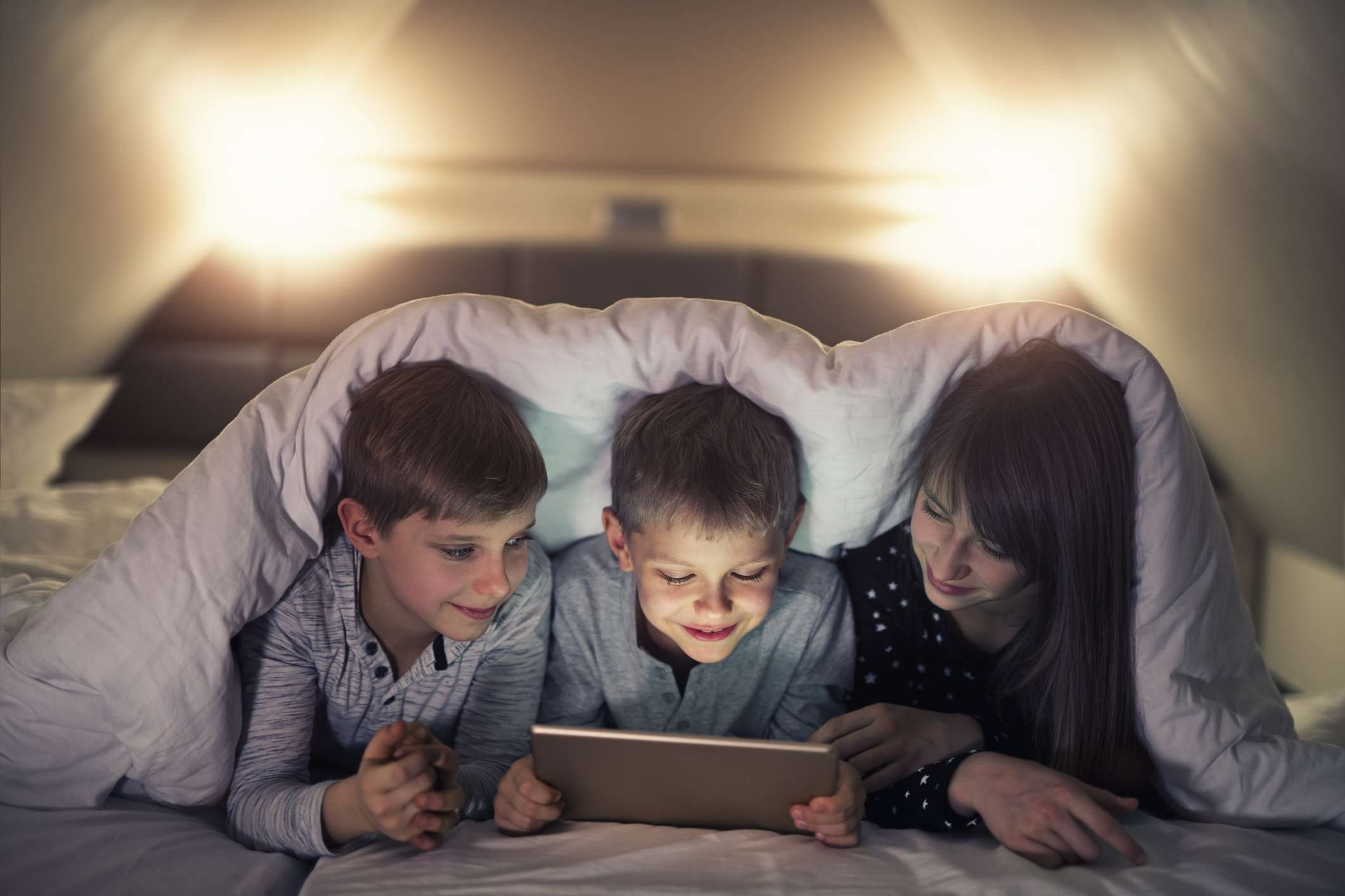 Three children looking at a tablet in bed