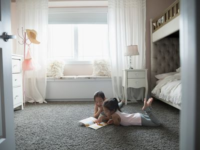 Two little girls laying on carpet floor