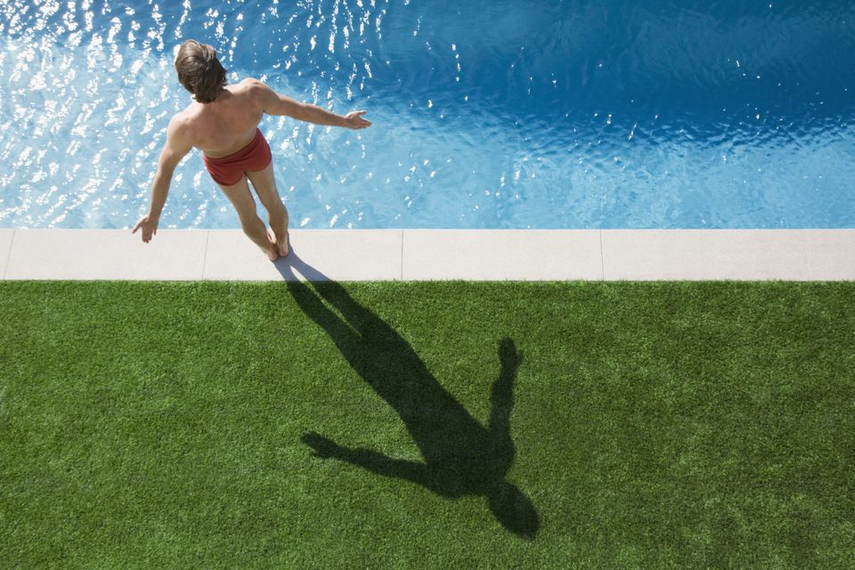 Man about to dive into swimming pool