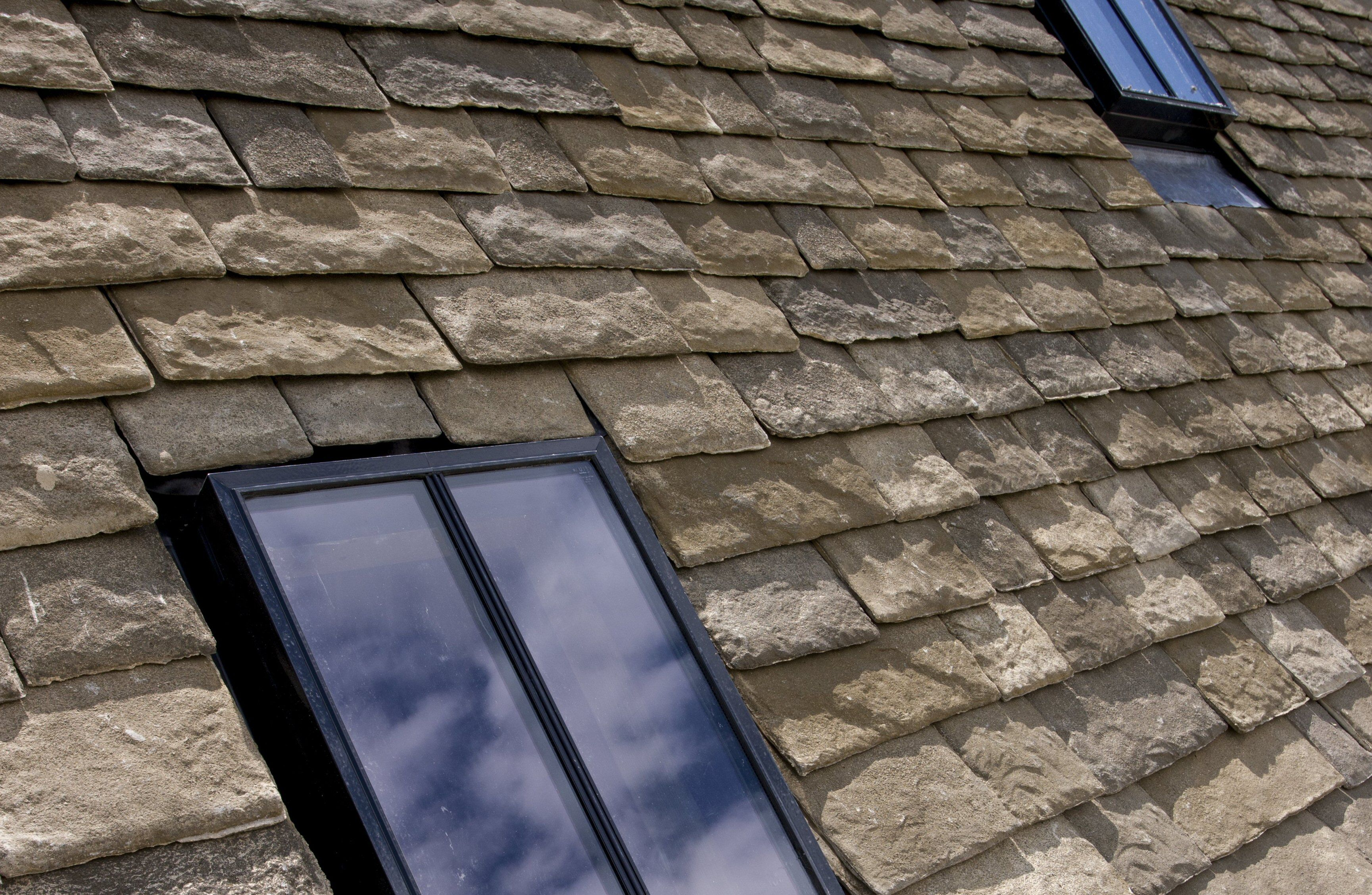detail of roof shingles that look like slate surrounding double-paned skylights