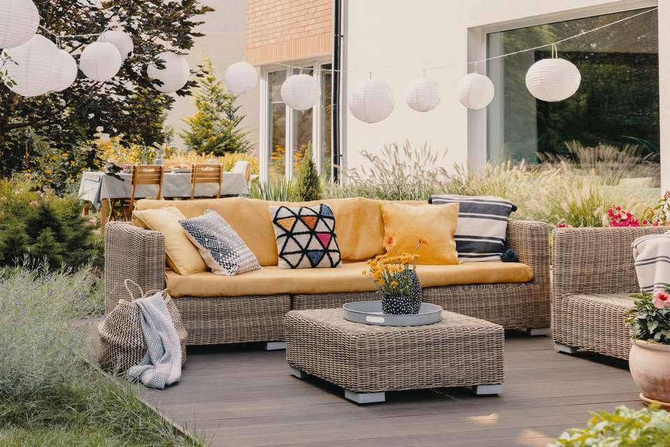 Flores en la mesa de mimbre cerca del sofá con cojines estampados en la terraza con linternas. Foto real