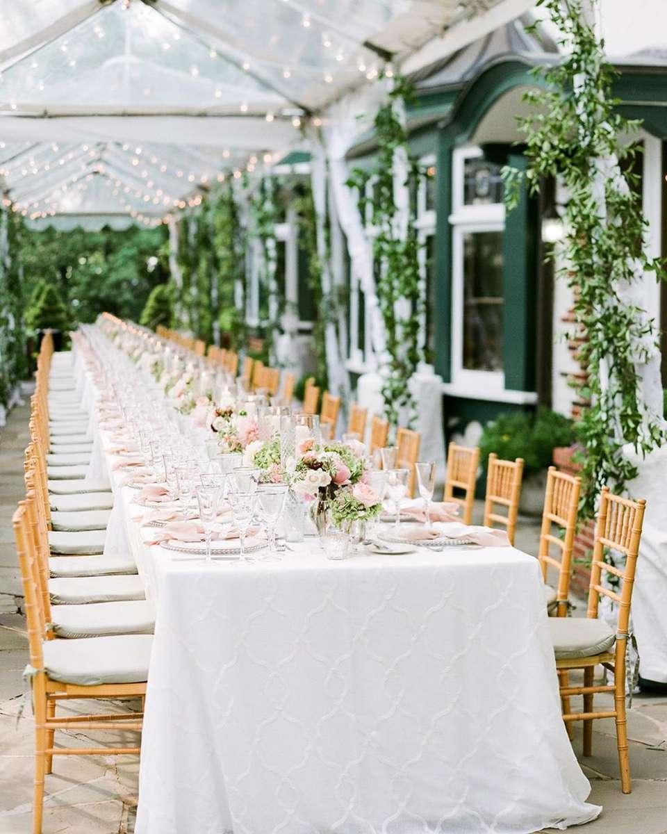 Mesa de boda larga con mantel blanco