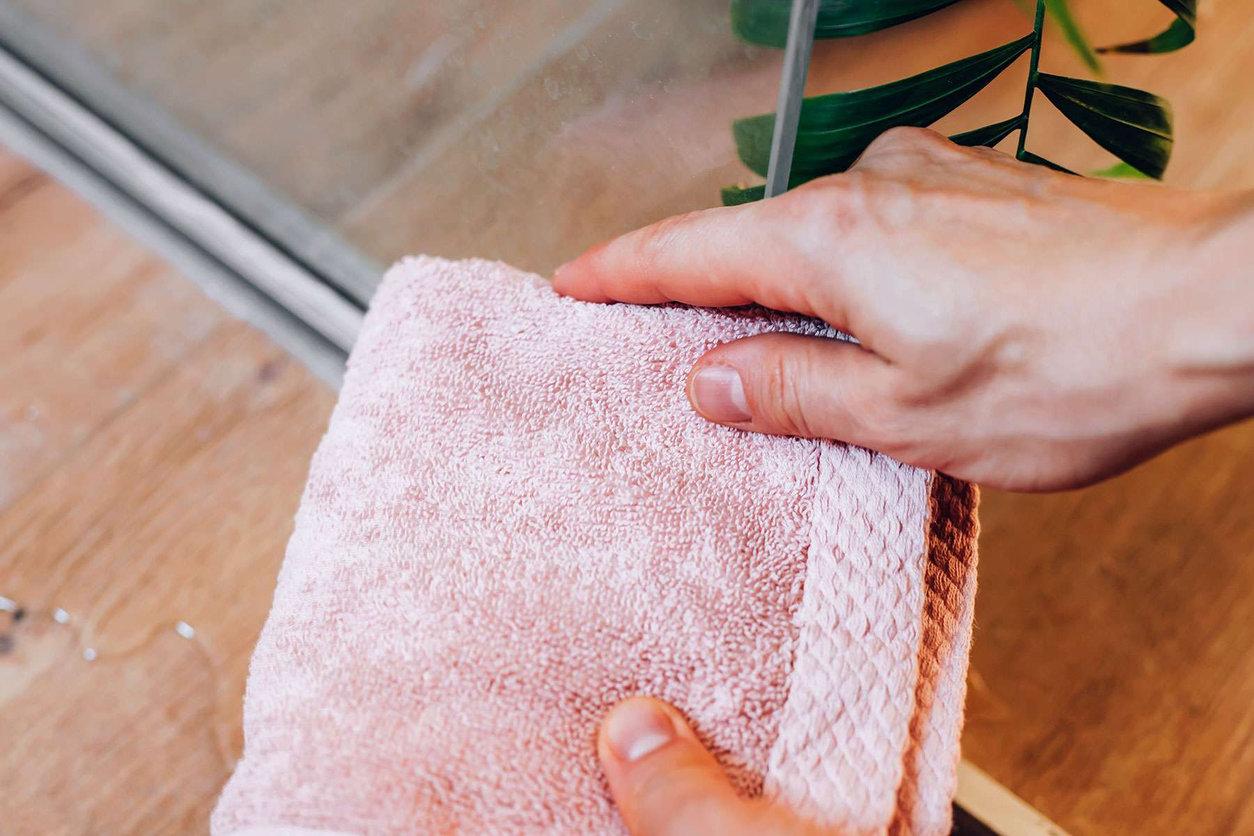 Glass shower door tracks dried with old pink towel