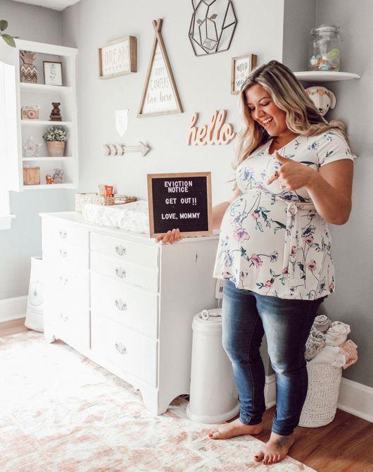 Mujer embarazada con un tablero de letras que dice aviso de desalojo