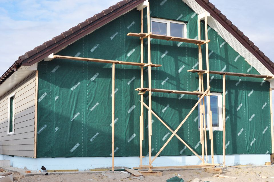 Building, Repair, Remodeling House with Plastic Siding and Insulation Membrane, Mineral Wool.Foundation insulation with styrofoam. Installing Rigid Foam Insulation.