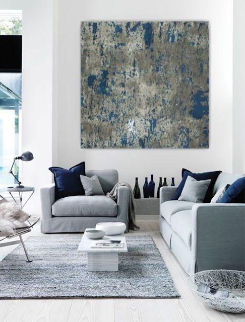 Habitación con capas de gris y azul en muebles y arte