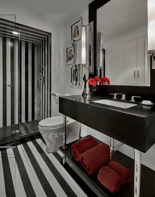 Baño blanco y negro a rayas con detalles en rojo