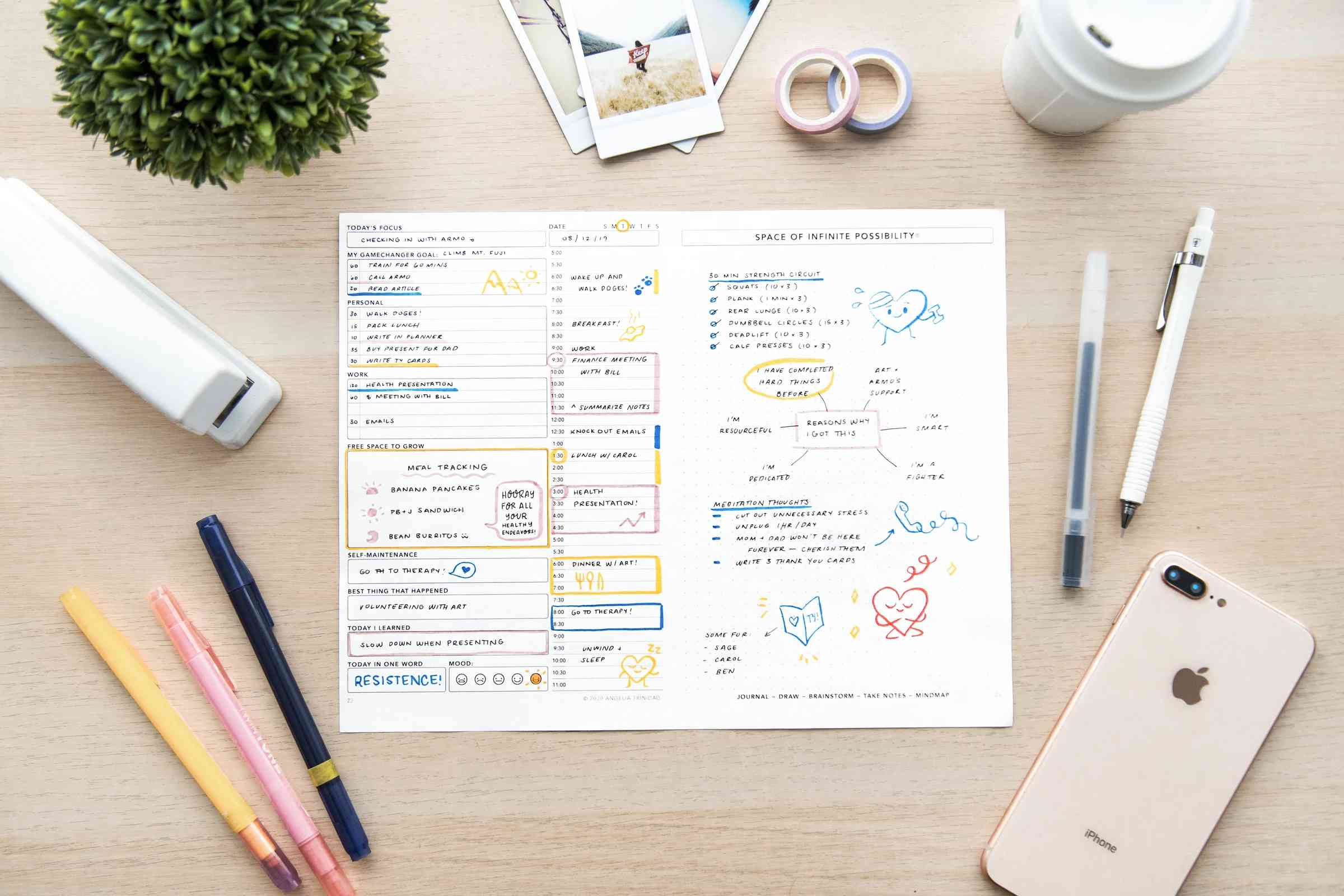 A daily planner on a desk with a phone and office supplies