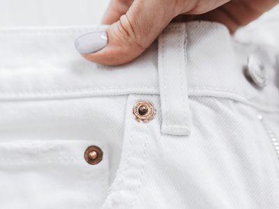 Rose gold metal trim near white jean belt loop