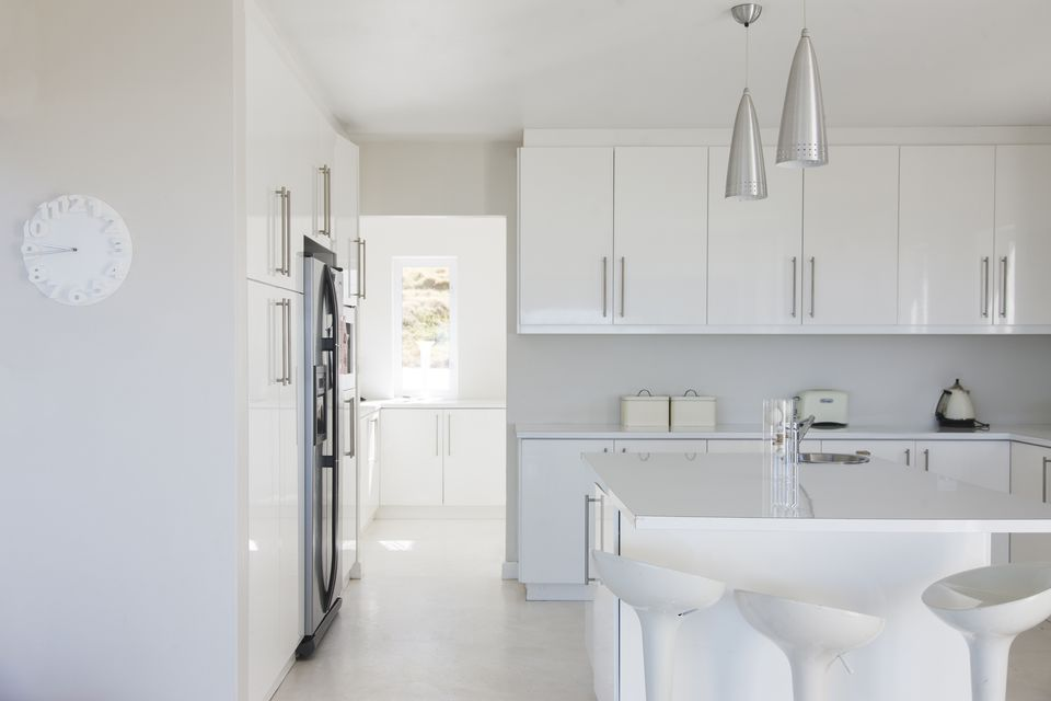 Modern white and clean kitchen interior with stools at counter