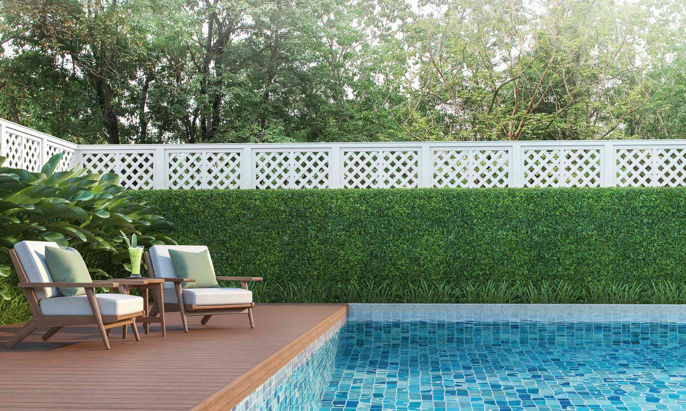 A backyard pool surrounded by shrubbery and a white lattice fence.