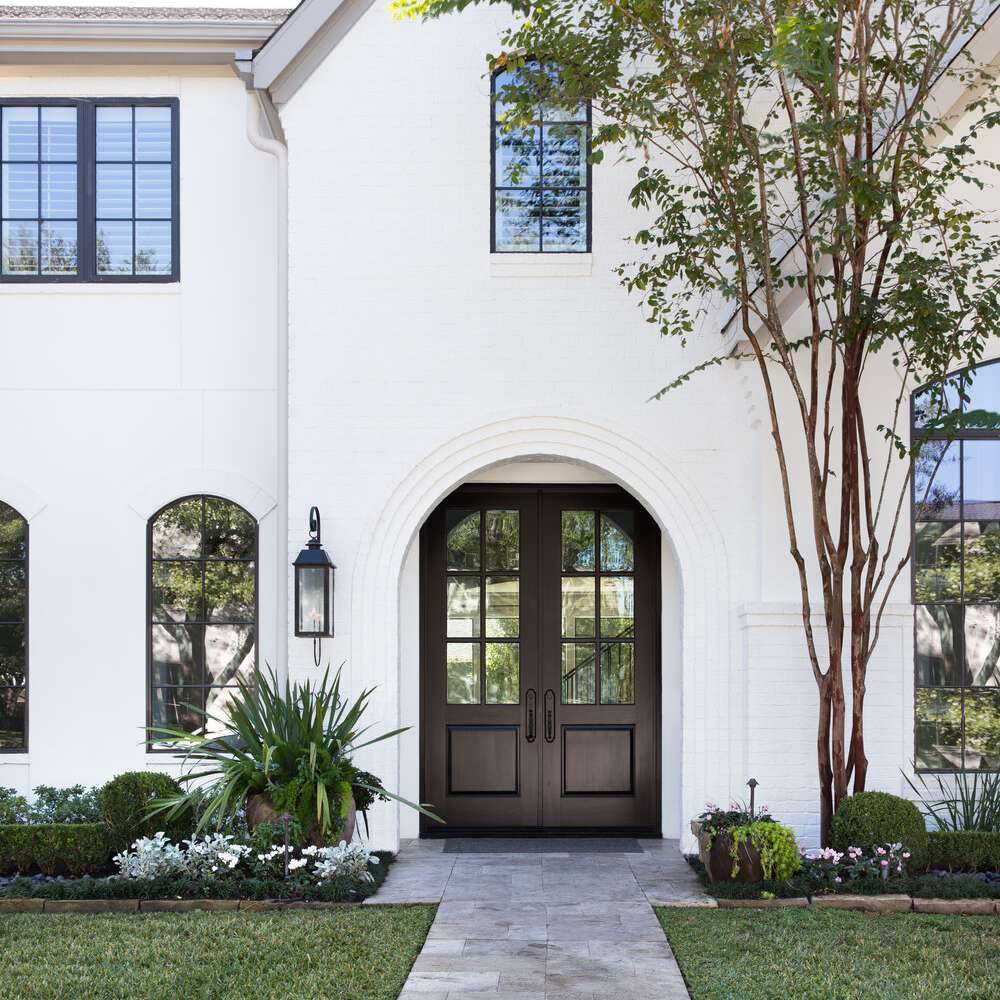 front yard with stone path and arched entryway leading to dark wooden set of double doors,
