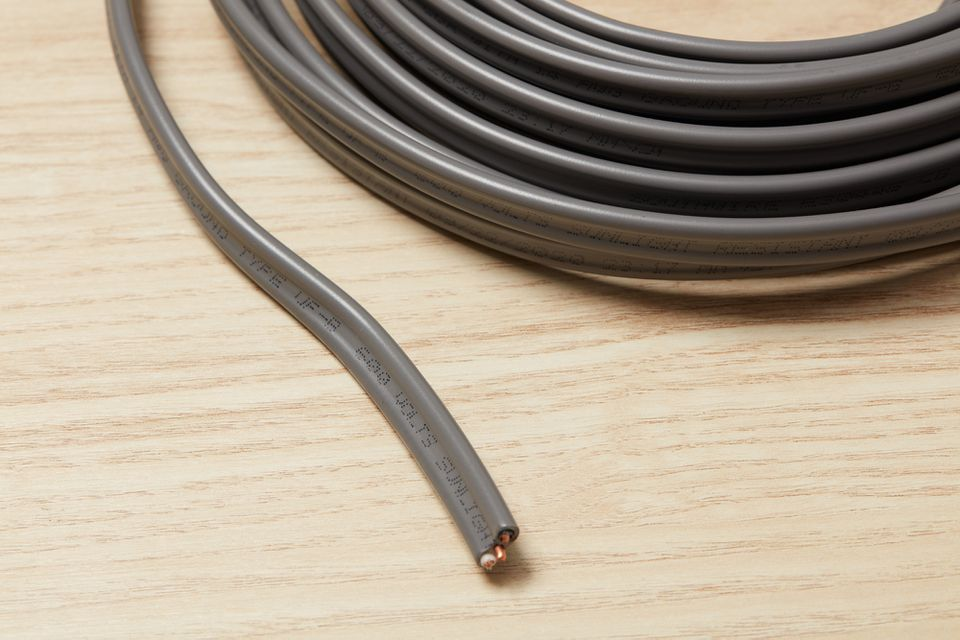 Electrical wire for underground circuit cable on wooden surface closeup