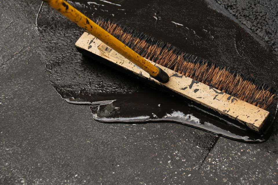 A broom and tar used to seal asphalt driveways