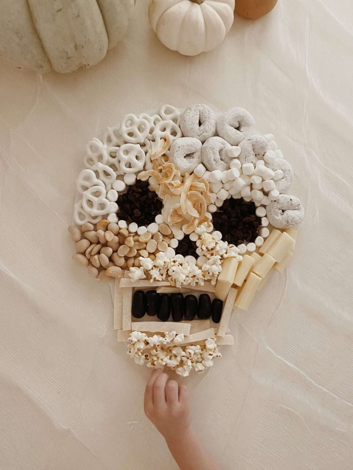 A hand reaching for a skeleton shaped snack board