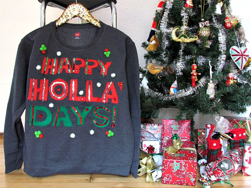 An ugly Christmas sweater by a Christmas tree