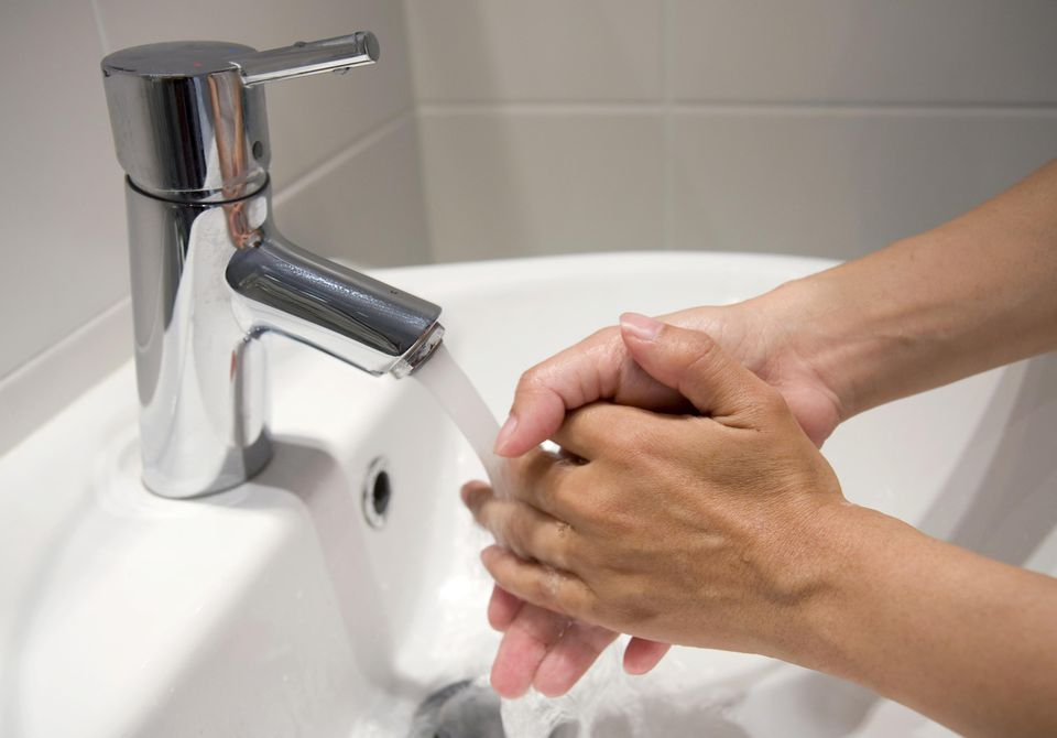 Person washing hands in modern bathroom.