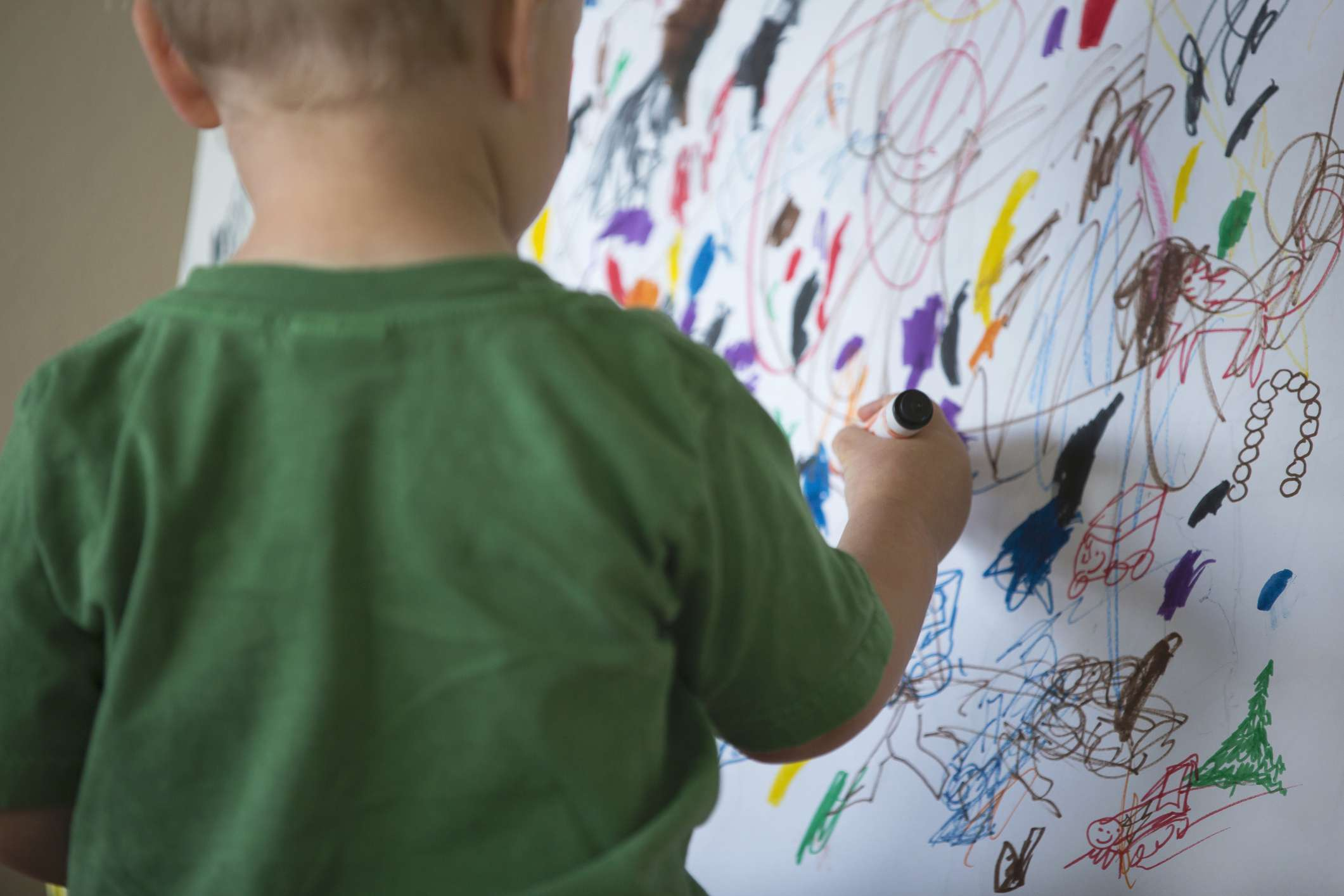 Toddler using a marker and drawing on a wall.