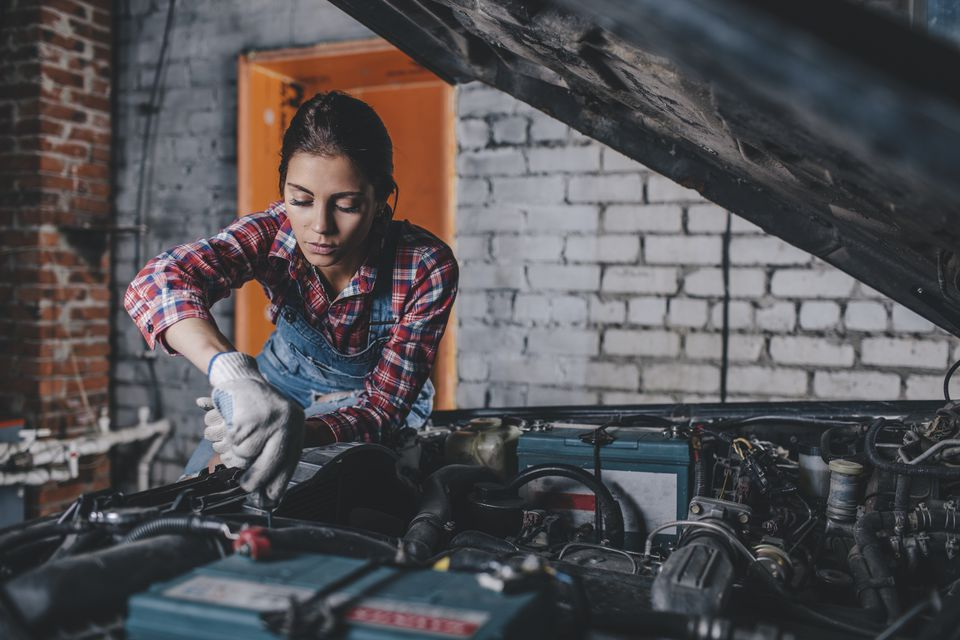 Female mechanic repairing car engine at garage