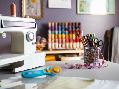 Craft room with sewing machine on table with brushes and markers stacked in can