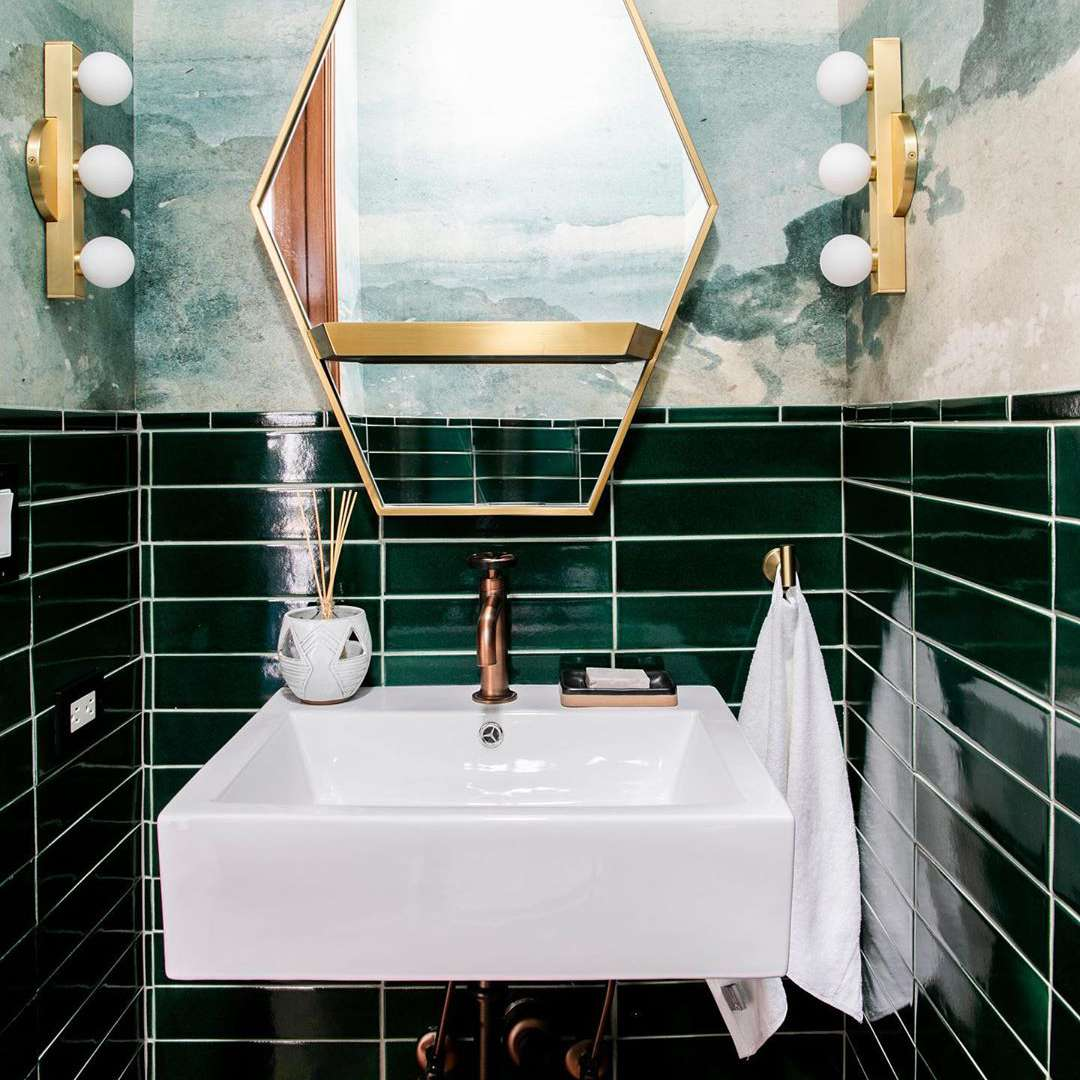 Dark green tiles and wallpaper in a bathroom