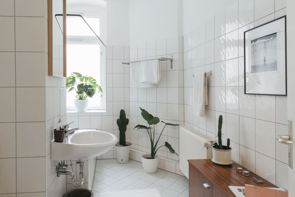 White wall mount sink with exposed pipe in a white bathroom