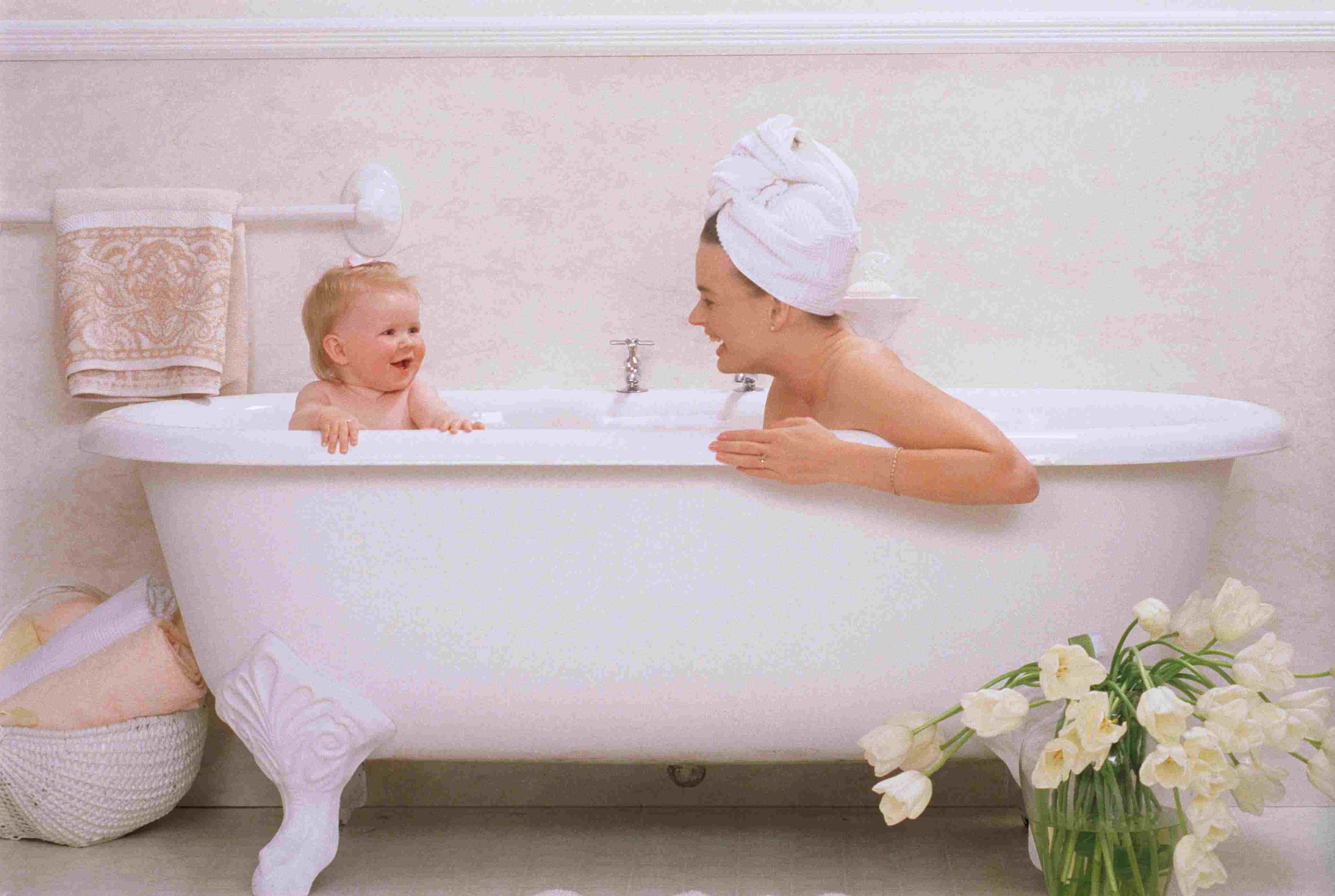 Mom and baby in a white claw-foot tub with a vase of white daffodils on the floor.