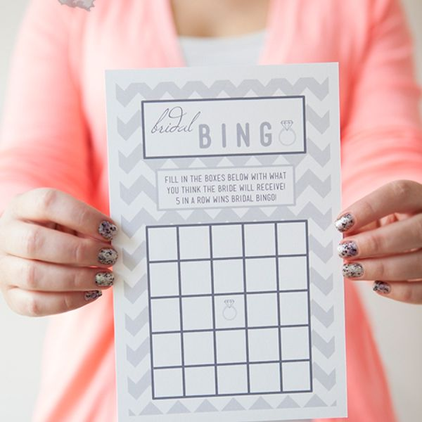 a woman holding a bridal shower bingo card