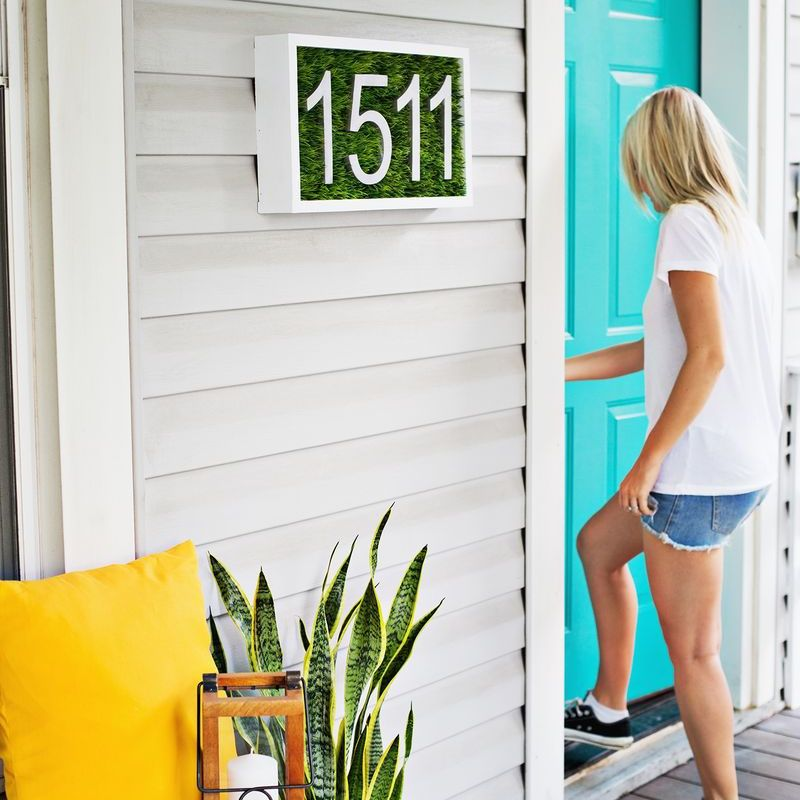 Modern house numbers on a faux grass board.